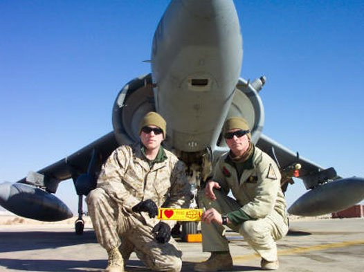 Photo of 2 fighter pilots in front of a fighter jet together holding up a DP bumper sticker