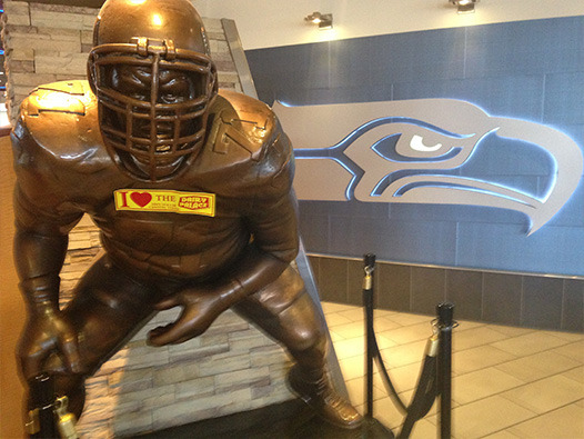 Photo of a DP bumper sticker stuck to the bronze statue of a Seattle Seahawks football player