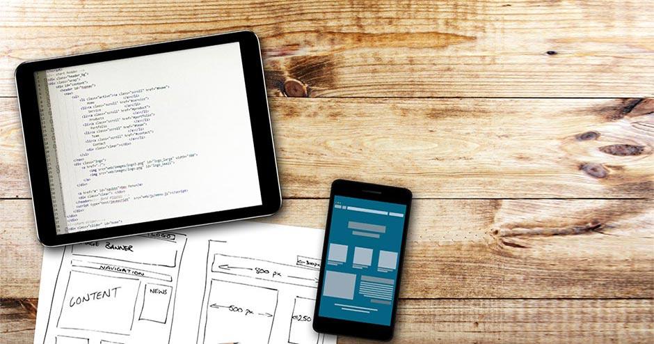 imagem de tablet, um smartphone e uma folha de papel