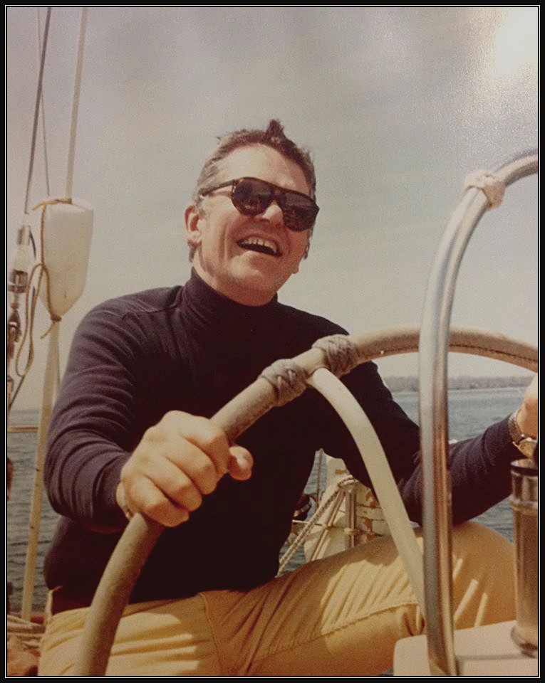 Photo of Mack Woodruff at the helm of a sailboat.