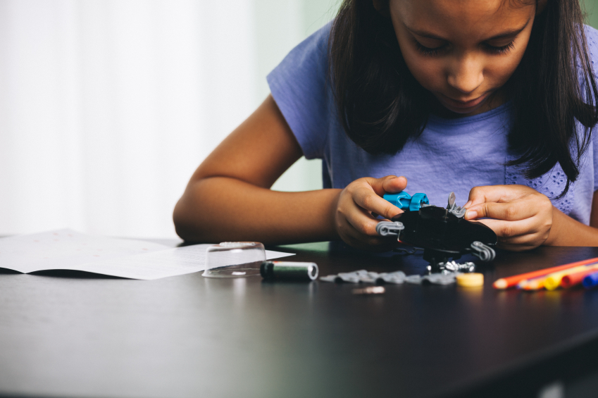 Photo of girl working intently on robotics project