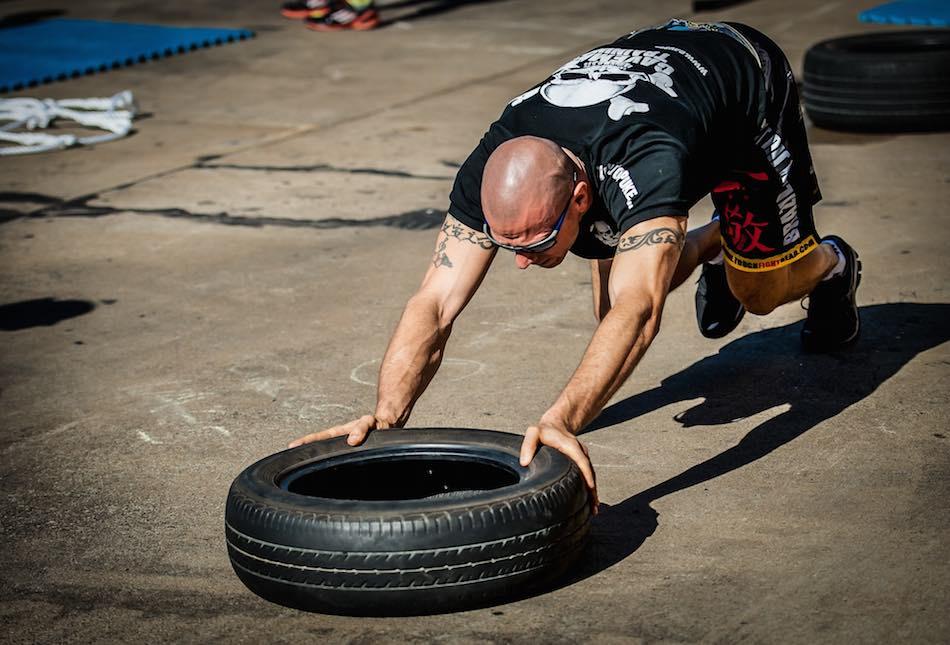 man pushing a tire