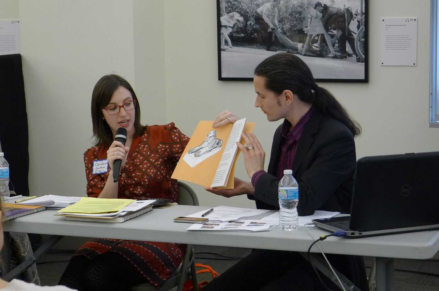 Photo of Christena Gunther holding up a document during a presentation.