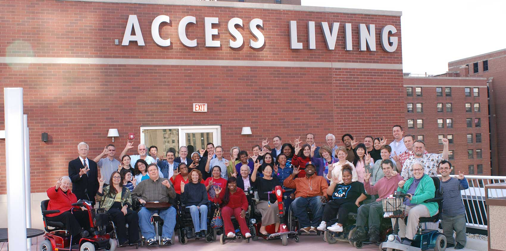 Photo of large group posing in front of the Access Living building.