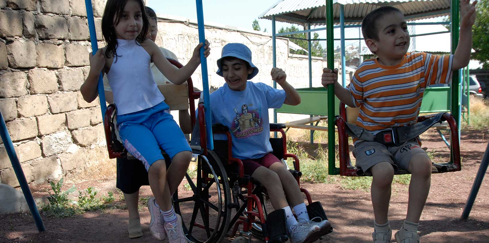Photo of children with disabilities playing on a swing set.