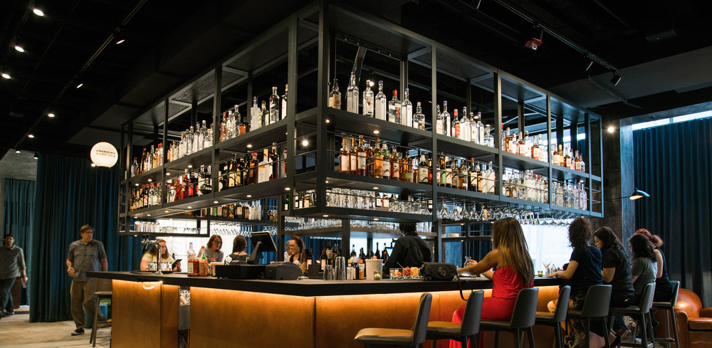 photo of bar at Front Bar. a bar counter set up in the center of the room with bottles above and people sitting on stools around the bar.
