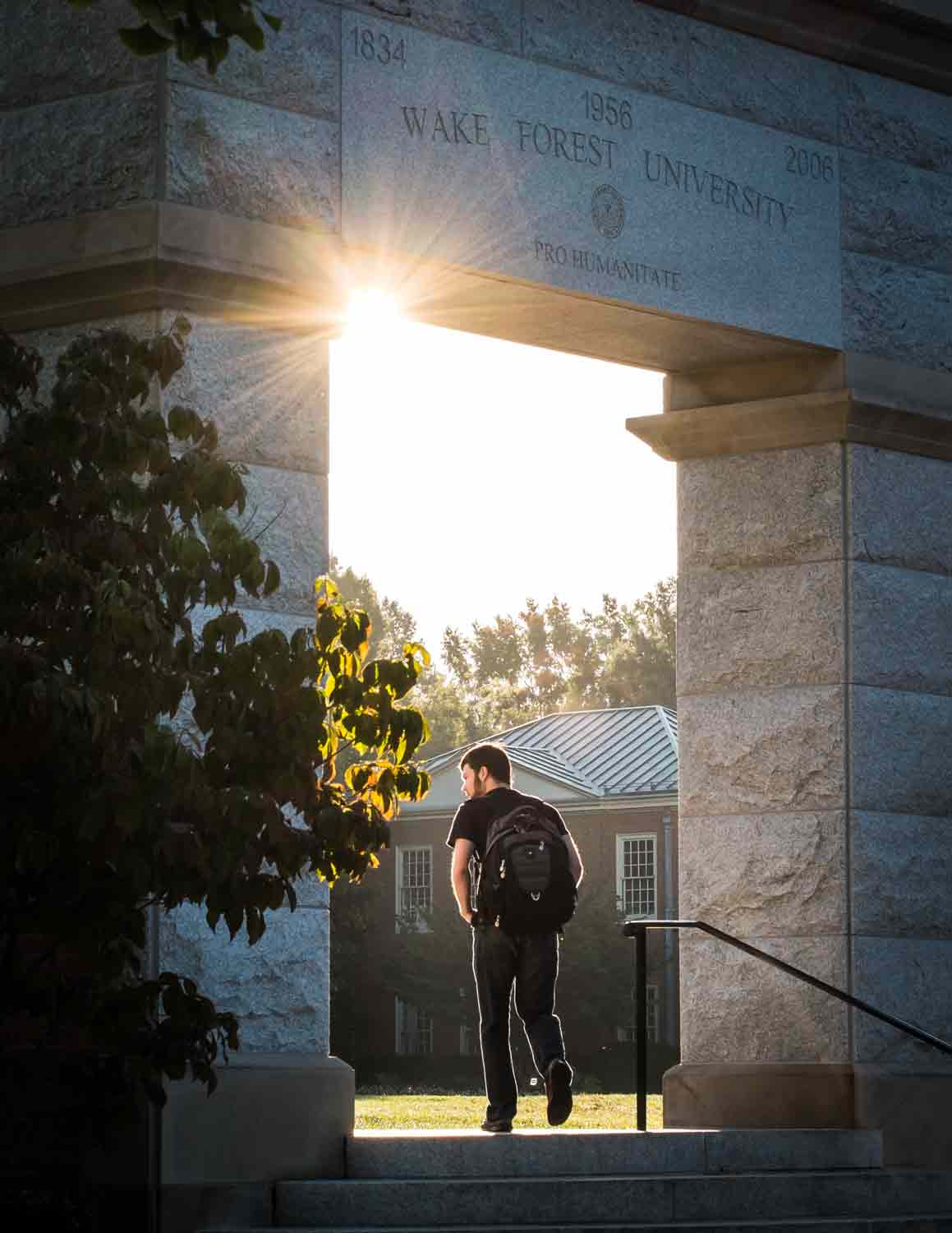 A student walks through the arch on Hearn Plaza on the campus of Wake Forest University
