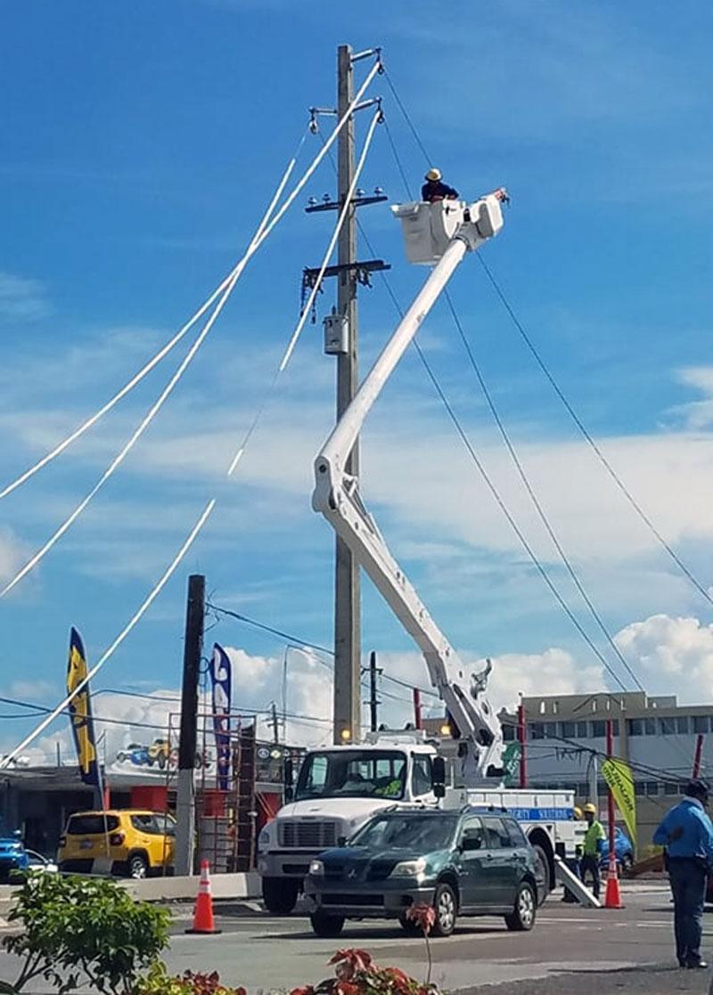 Hombre arreglando cablería del sistema eléctrico de Puerto Rico.