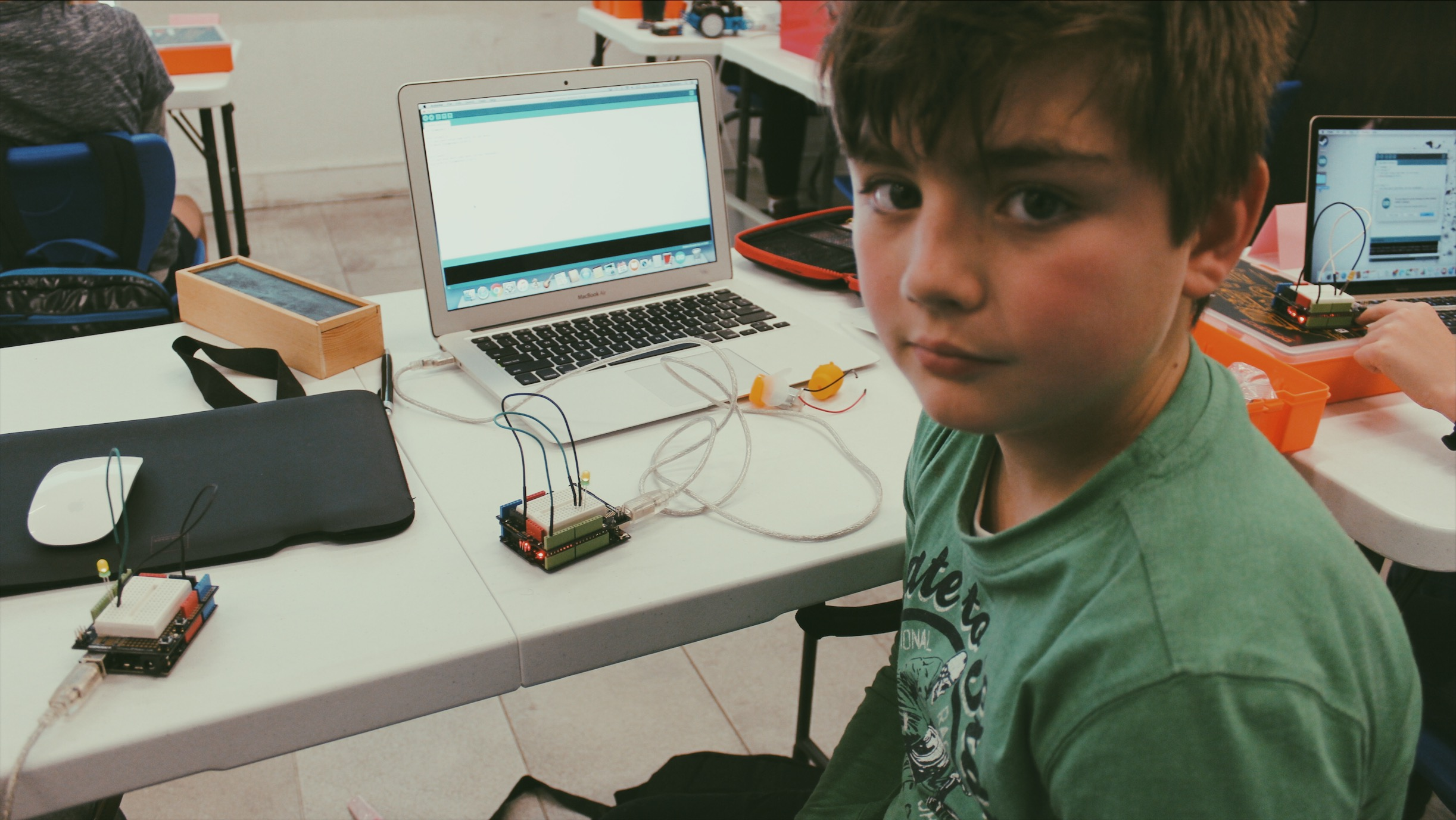 Lemonade Stand Kids Coding: a boy shows off his Arduino