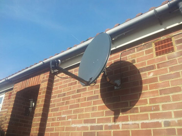 Picture of a satellite dish on brickwork