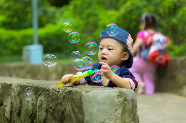 Boy playing in park with bubbles