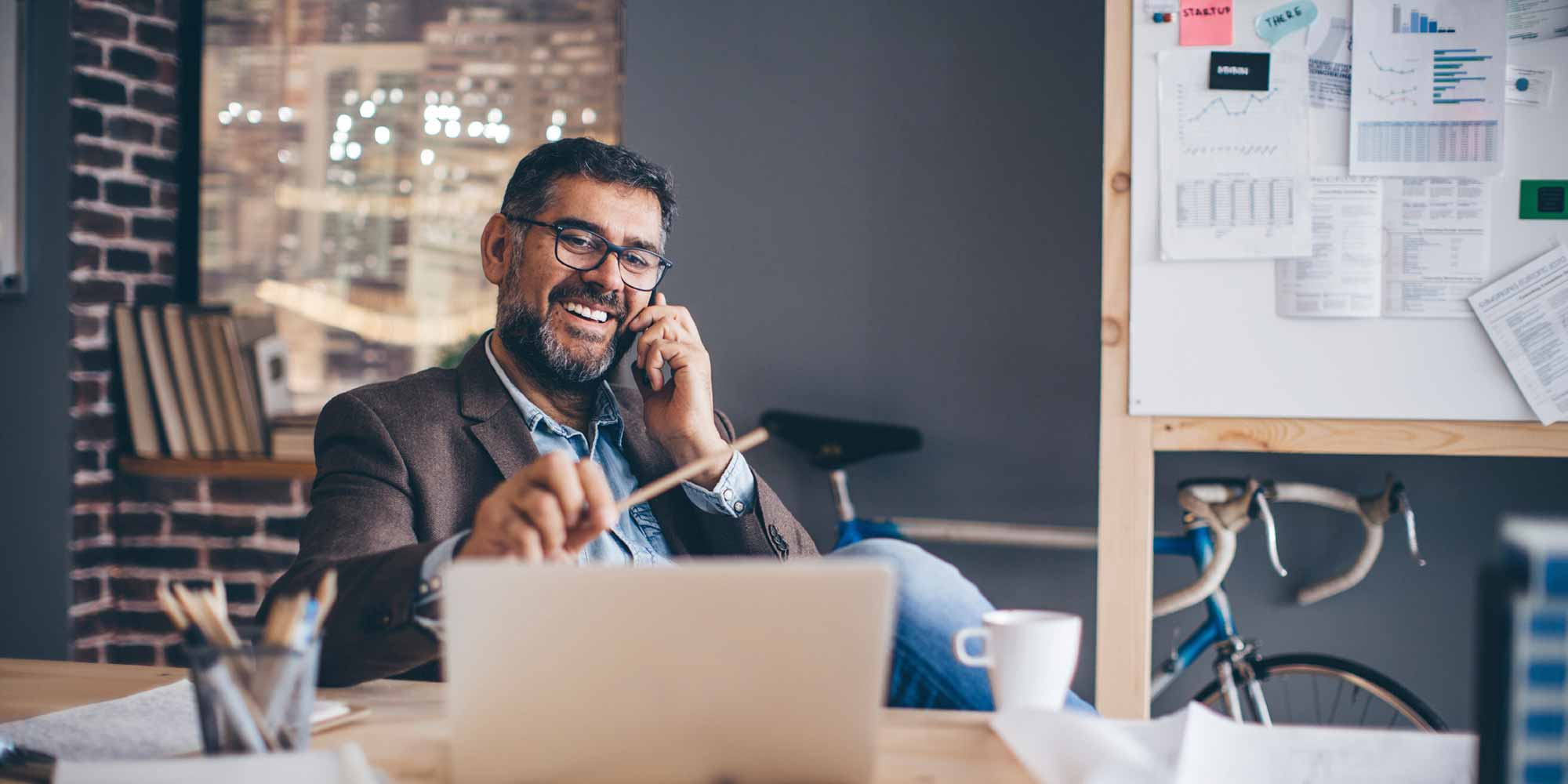smiling businessman on phone at desk in front of laptop