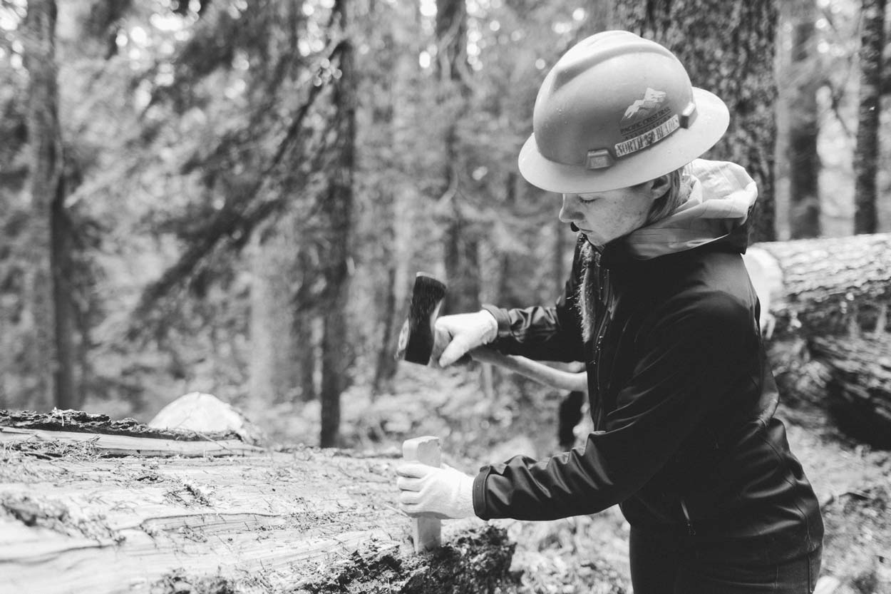 Uphill Designs volunteer hammering a wedge
