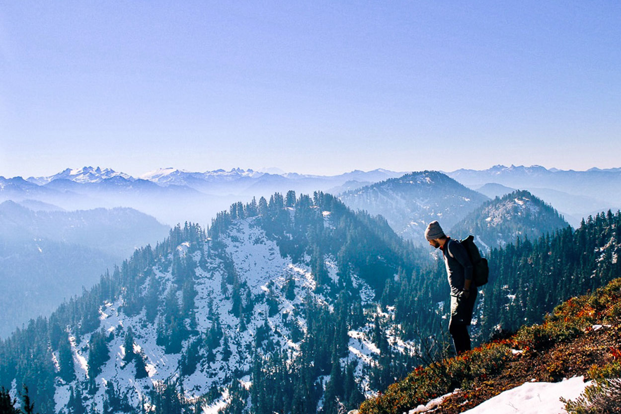 Hiking adventurer looking out at snowy mountains