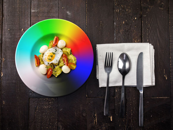 A rainbow colour plate with food on it showing how it affects the look of food.
