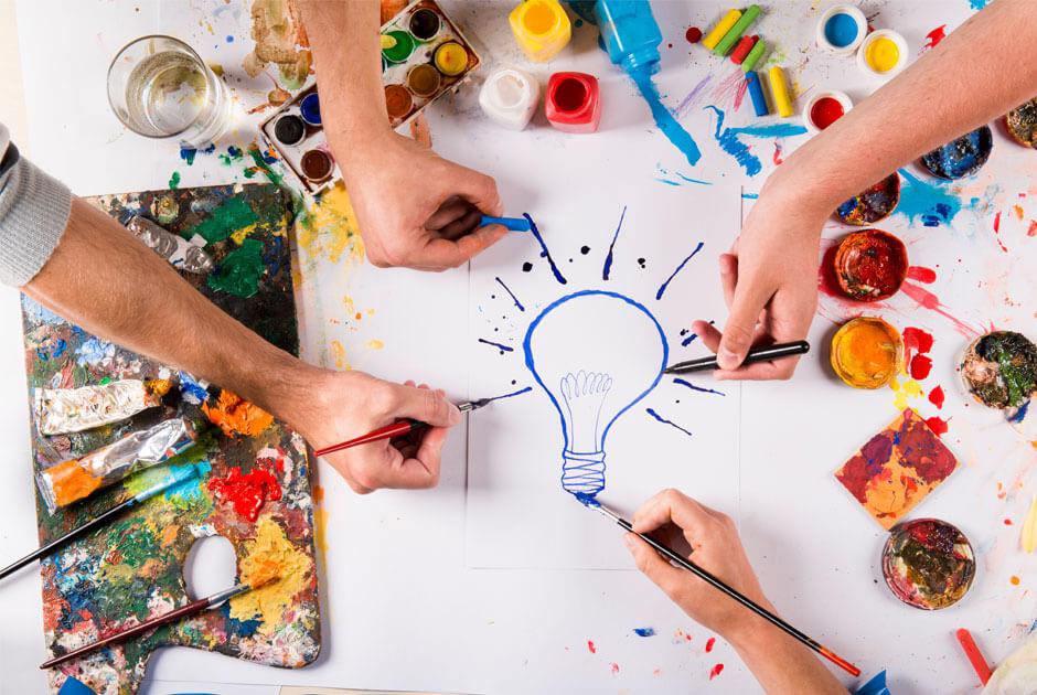 Imagem com mãos desenhando uma lâmpada.