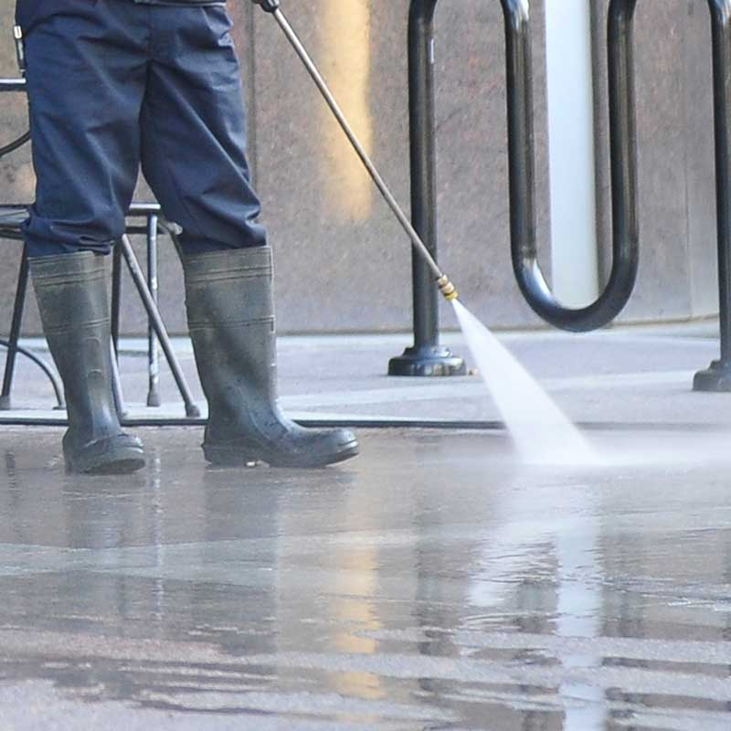 Pressure washing a commercial building front entrance.