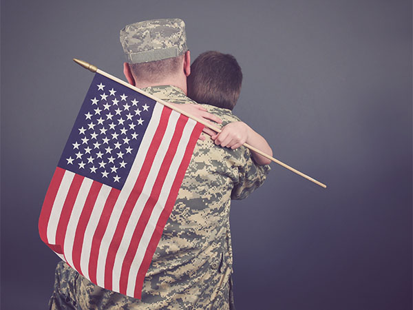 US soldier hugging his son