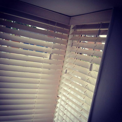 white wooden venetians fitted in rectangular bay window