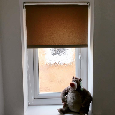 light brown roller blind fitted in small window
