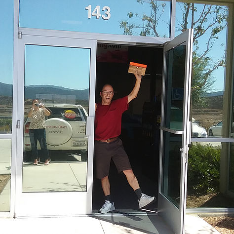 Image of owner in front of office doors with reflective window film applied.