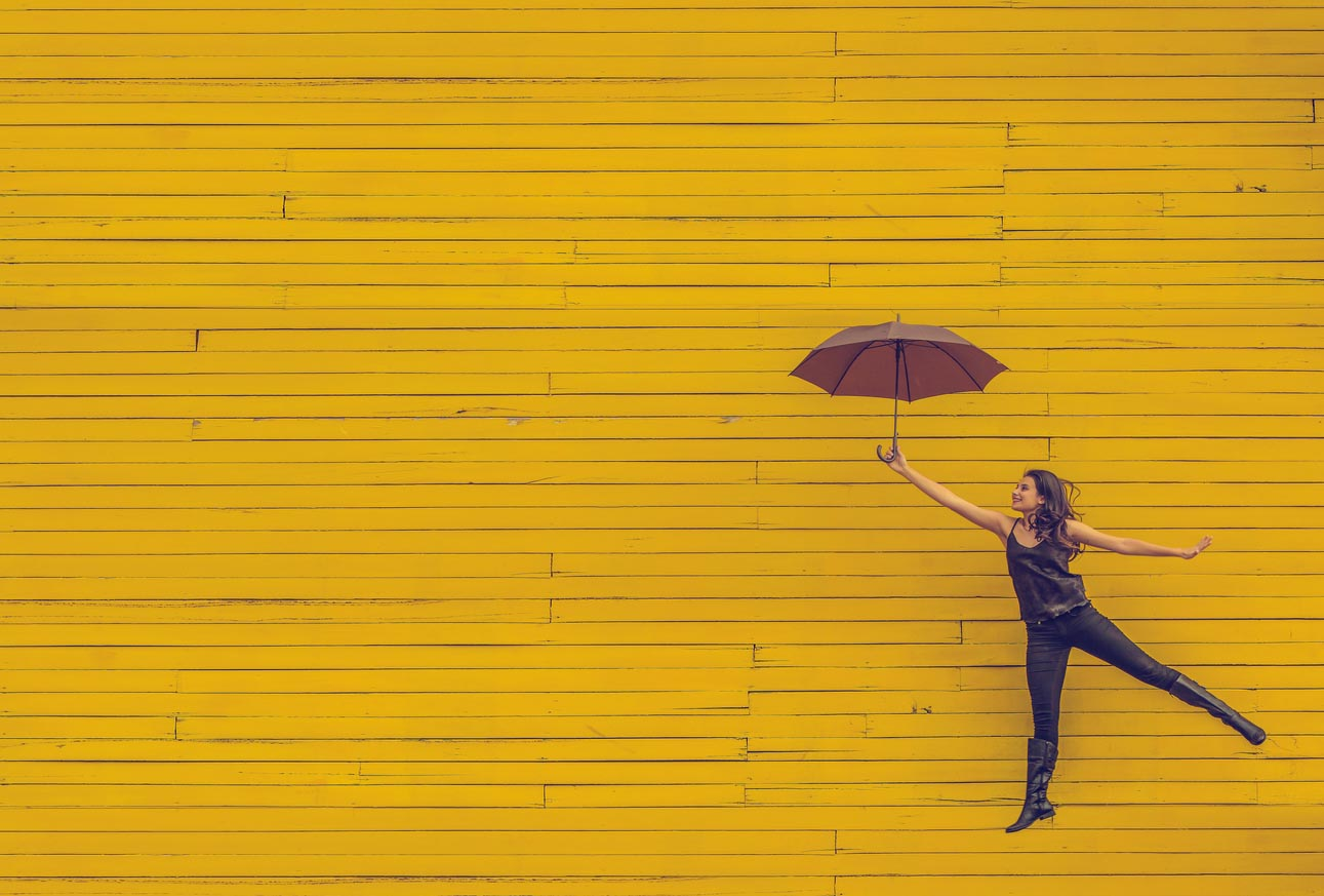 Woman with parasol jumping against yellow wall