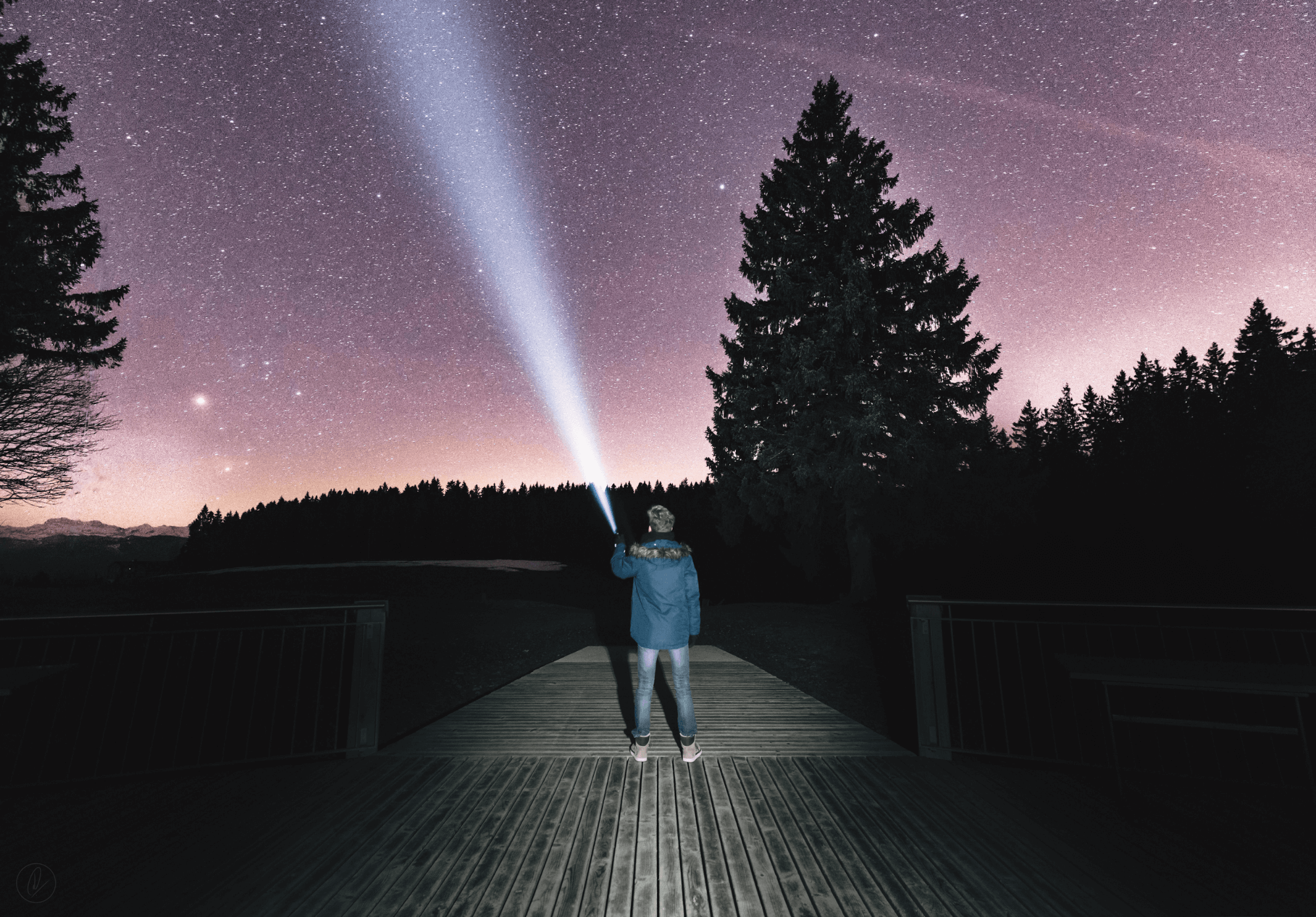 A man pointing a flashlight up at the night sky