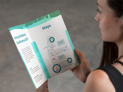 Photo of a person holdin a conference brochure with indoor maps