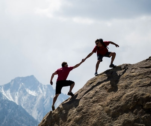Two men helping each other climb a mountain