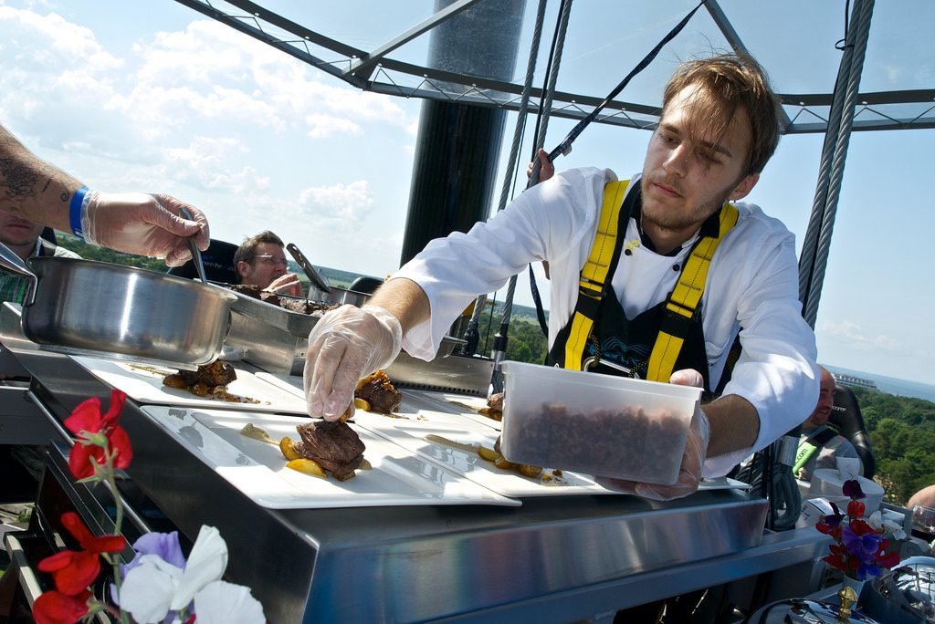 chef plating food at dinner in the sky