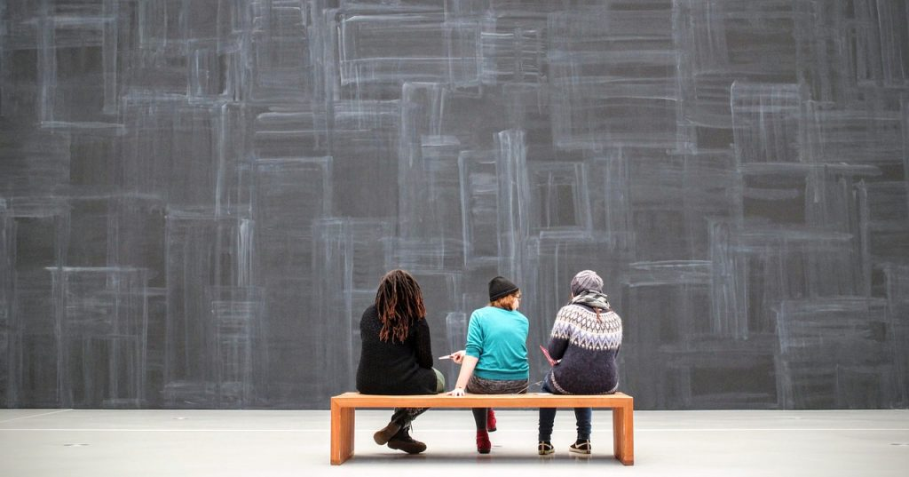 3 people sitting in front of a chalk wall