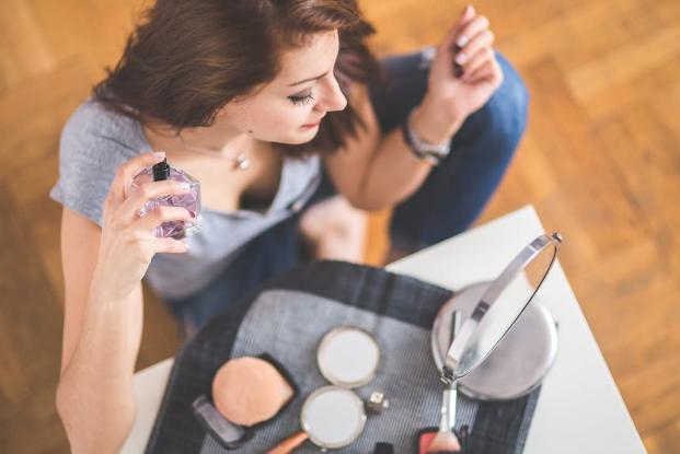 woman putting on perfume and makeup
