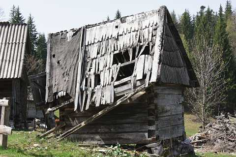 Broken down hut with a patched up roof