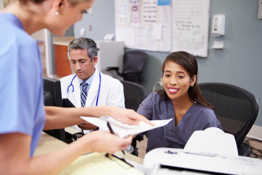 Doctors and nurses discuss a patient's chart