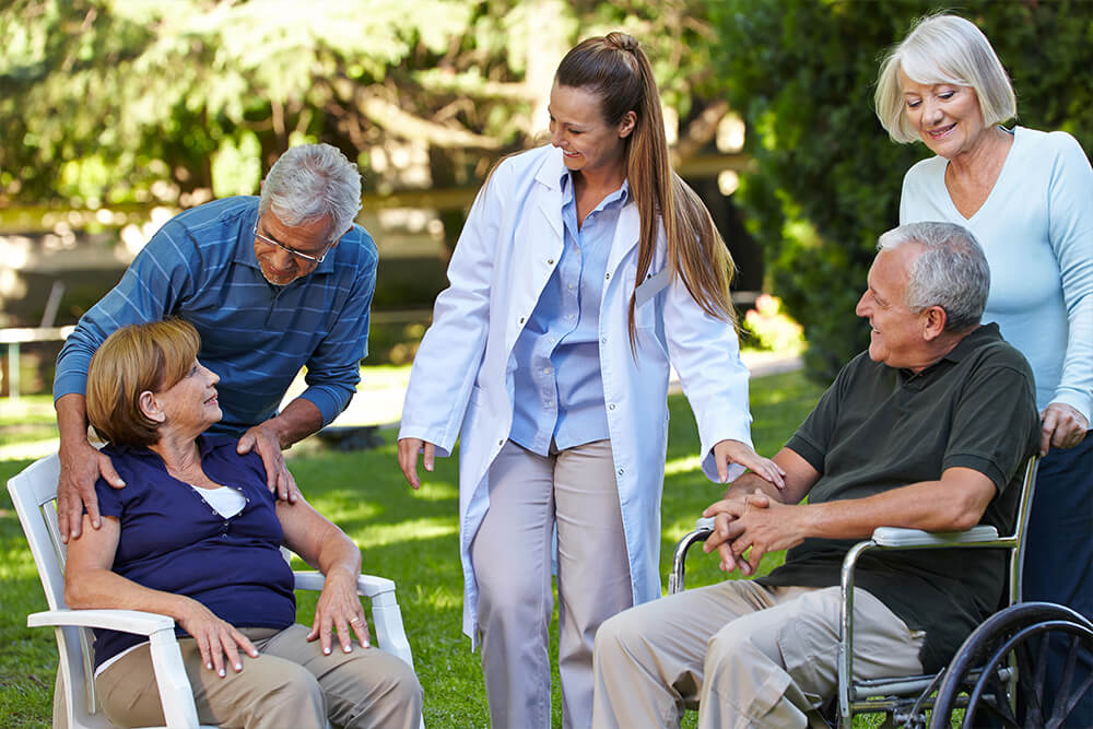 A group of nursing home residents and staff interacting outside