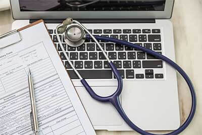 HIPAA compliance laptop with stethoscope and medical records