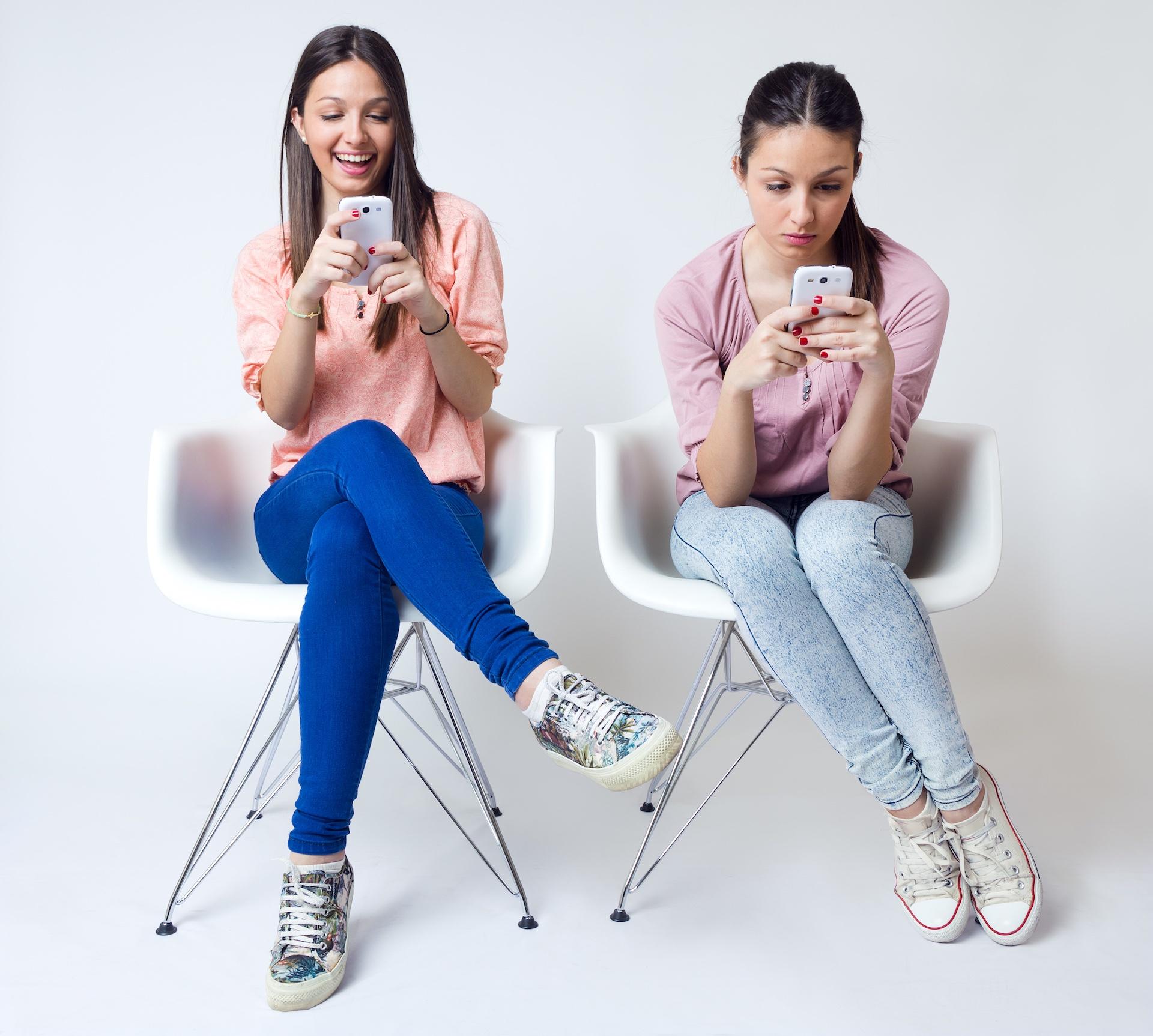 Two Girls Using Smartphones