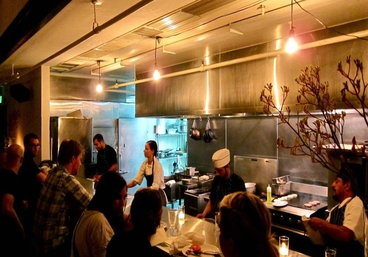 open kitchen restaurant with 4 cooks and people at the bar