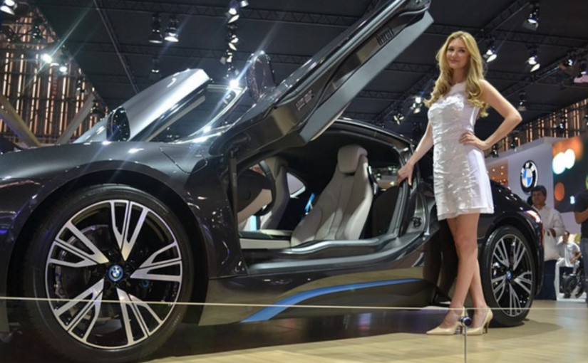 woman standing next to a bmw at the car show