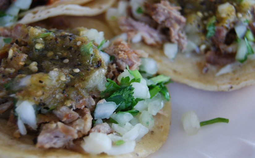 close-up of carnitas tacos with salsa on them