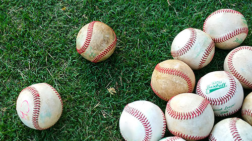 Photo of Baseballs on Grass. LakePoint Sports