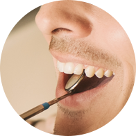 Photo of a man with a dental mirror in his mouth