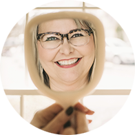 Photo of a smiling woman's reflection in a handheld mirror