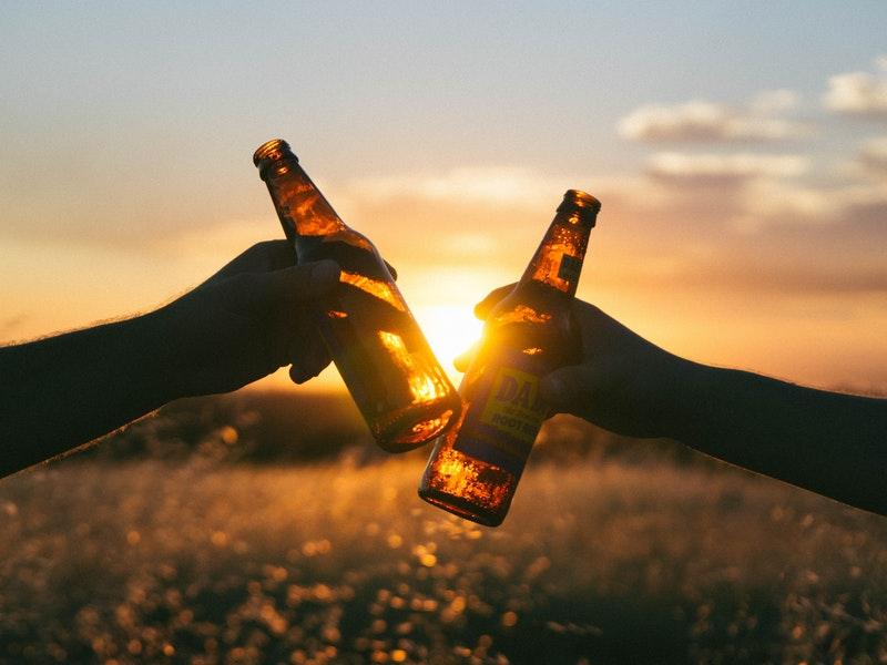 2 people hitting Beer bottles together