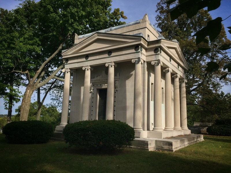 columned mausoleum surrounded by shrubs and trees