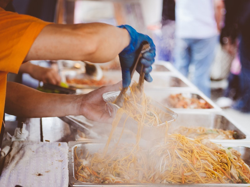 man's arms serving french fries at festival