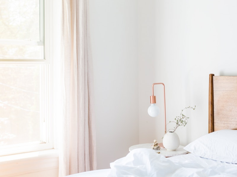 white bedroom with side table and window