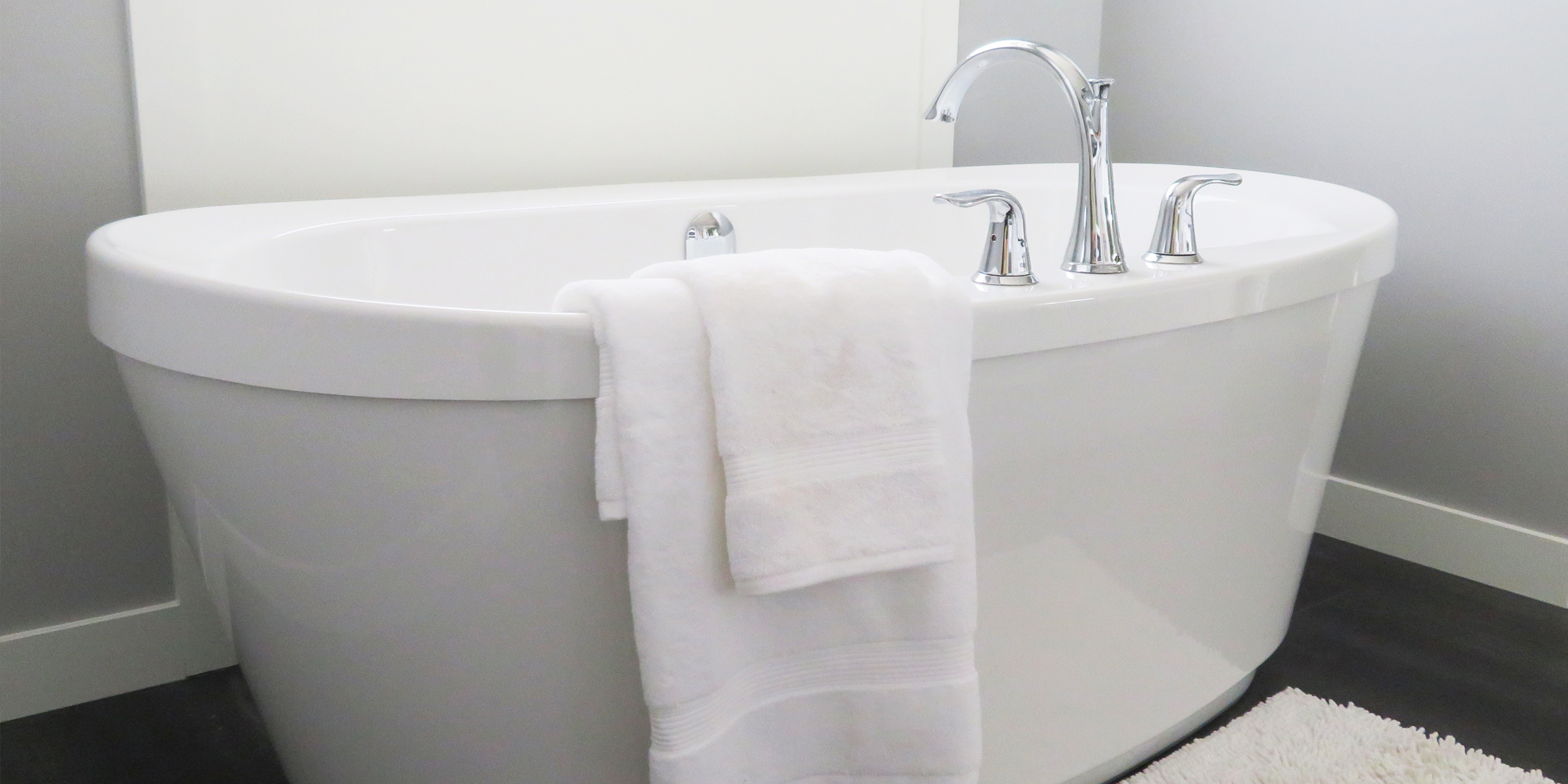 Fluffy white towel hanging on a bath tub