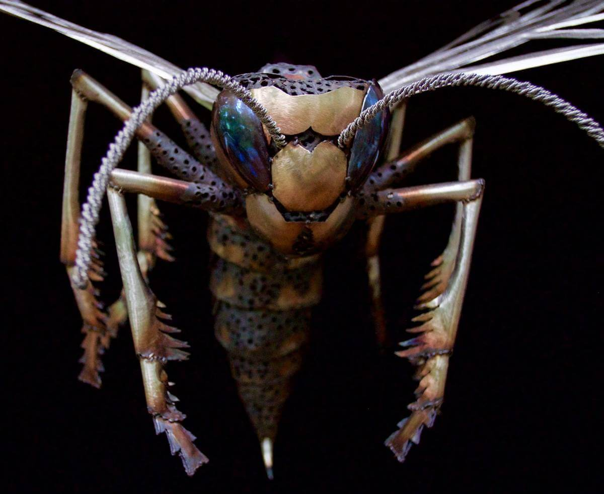 Close up of the face and antenna of a metal wasp sculpture