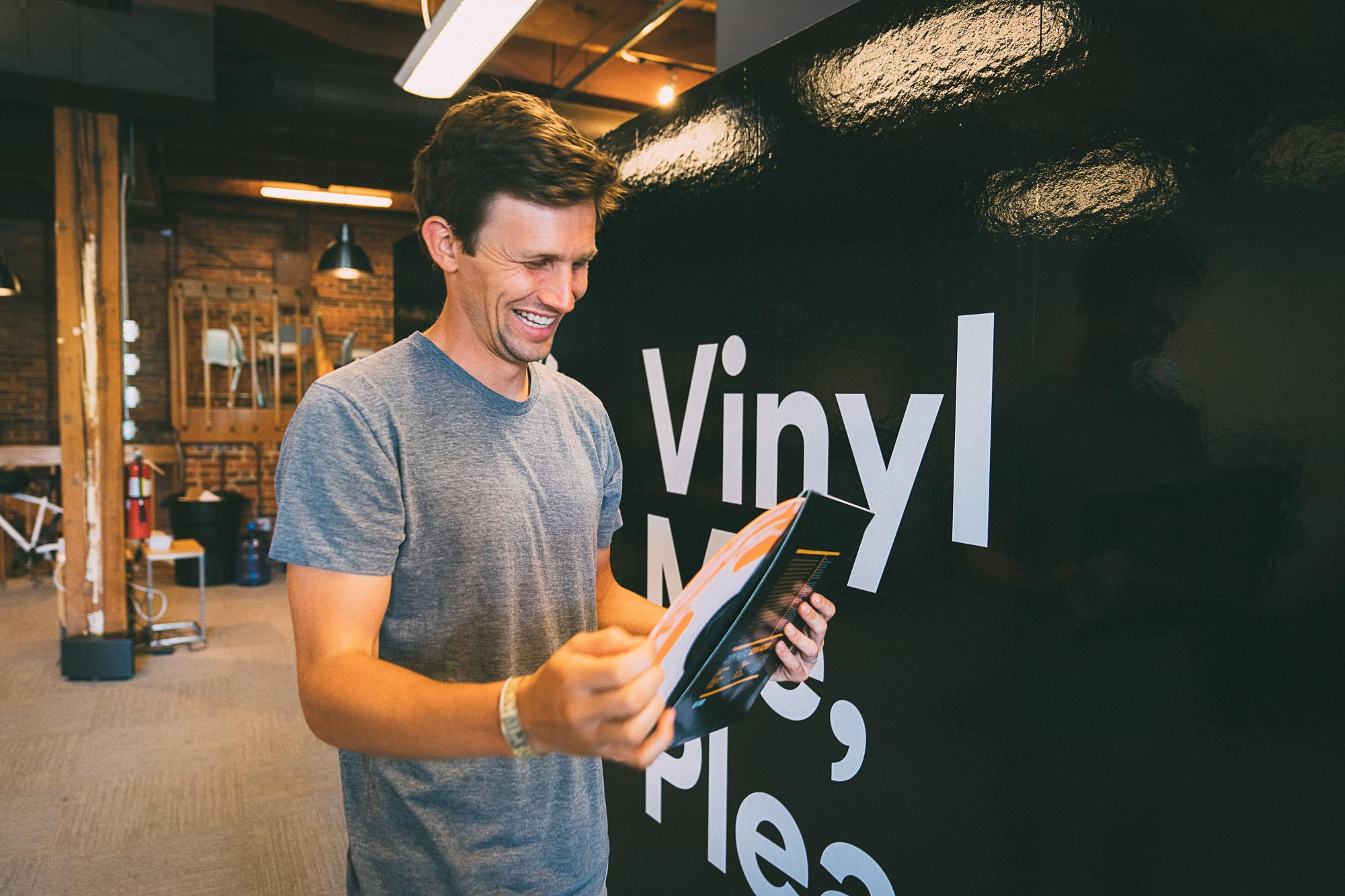 A man smiles while holding a vinyl record in Denver.